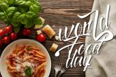 top view ízletes bolognai tészta paradicsommártással és parmezán fehér lemez közelében összetevők és evőeszközök fa asztalon, világ élelmiszer nap illusztráció