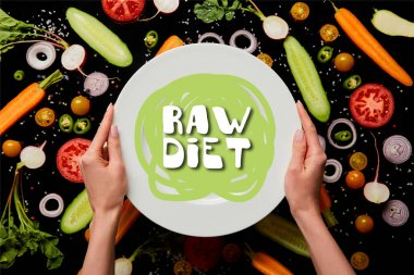 Cropped view of woman holding round plate with raw diet illustration on vegetable pattern background isolated on black stock vector
