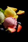 selective focus of delicious lemon, berry and mint ice cream balls isolated on black