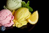 Photo delicious lemon, berry and mint ice cream balls isolated on black