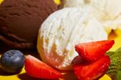 zblízka pohled na chutnou hnědou a bílou zmrzlinu s bobulemi a mátou
