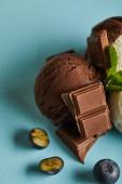 zblízka pohled na chutnou hnědou zmrzlinu s bobulemi, čokoládou a mátou na modrém pozadí