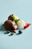 chutná hnědá a bílá zmrzlina s bobulemi, čokoládou a mátou na modrém pozadí