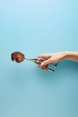 Cropped view of woman holding scoop with chocolate ice cream on blue background stock vector