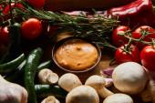 ízletes mártás tálban friss érett zöldségek, rozmaring és gomba közelében