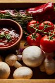 vynikající rajčatová omáčka v misce v blízkosti čerstvé zralé zeleniny, rozmarýnu a hub