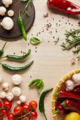 Fényképek felülnézet ízletes friss érett zöldségek, fűszerek, fűszerek és gombák fa asztalon