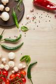 felülnézet ízletes friss érett zöldségek, fűszerek, fűszerek és gombák fa asztalon