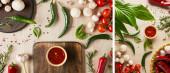 koláž z lahodné rajčatové omáčky v misce v blízkosti čerstvé zralé zeleniny, bylin, koření a hub na dřevěném stole