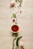 vrchní pohled na lahodnou rajčatovou omáčku v misce v blízkosti bylin a koření na dřevěném stole