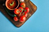 Draufsicht auf köstliche Tomatensauce in Schüssel auf Holzbrett mit frischem reifem Gemüse auf blauem Hintergrund