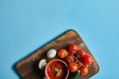 vrchní pohled na lahodnou rajčatovou omáčku v misce na dřevěné desce s čerstvou zralou zeleninou na modrém pozadí