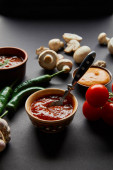 selective focus of tasty sauces in bowls near ripe cherry tomatoes, green chili peppers and mushrooms on black