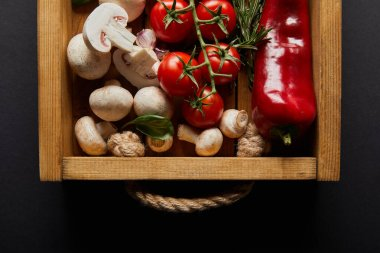 Top view of cherry tomatoes, chili pepper, mushrooms, cauliflower and garlic cloves near basil leaf and rosemary in wooden box on black stock vector