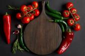 Fotografie vrchní pohled na dřevěnou řezací desku poblíž zralých cherry rajčat, stroužků česneku, rozmarýnu a zelených chilli papriček na černé