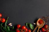 Fotografie vrchní pohled na zralá cherry rajčata, stroužky česneku, čerstvá rozmarýna, pepřová zrna, listy bazalky a zelené chilli papričky na černém