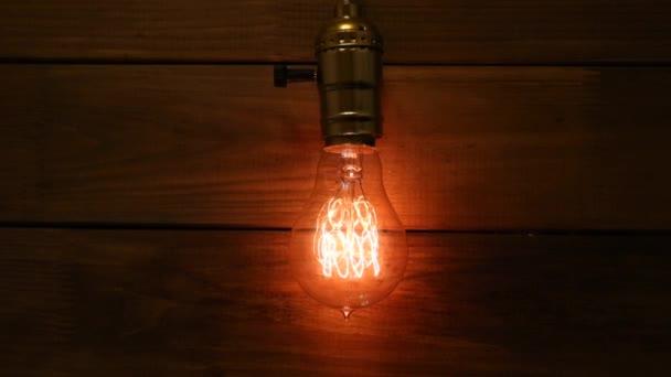 Staré vintage Edisons světlo žárovka svítí na pozadí Dřevěná prkna postupně rozsvítí a zhasne