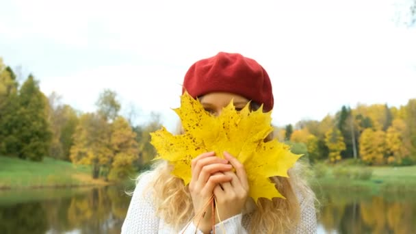glückliches Mädchen guckt aus gelben Ahornblättern und sieht verträumt aus