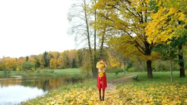 Happy girl throwing autumn leaves in the Park in slow motion
