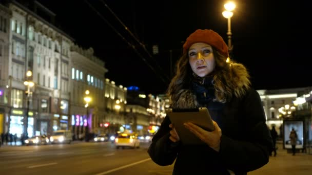 Mladá dívka Kavkazský s tabletem v ruce při pohledu na obrazovku a čeká a zastaví autobus, přijde. Na pozadí večerní město.
