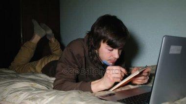 Mladý bělošský student dům leží na posteli a zapíše do poznámkového bloku z notebooku