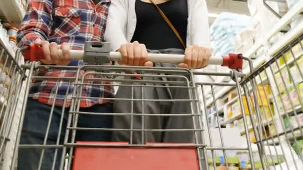 Young couple with a cart makes shopping in the supermarket, 4k.