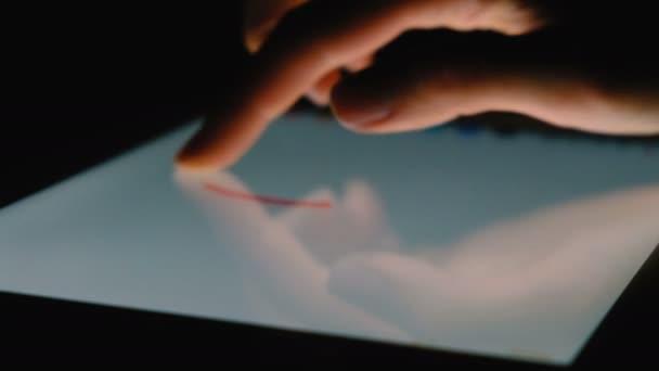 Finger maluje srdcem na tabletu v temné detail, 4k