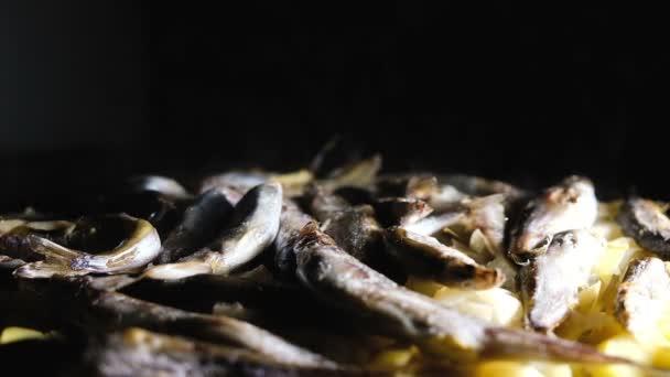 Fischcapelin mit Kartoffeln auf dunklem Hintergrund in einer Pfanne gedünstet, Zeitlupe.