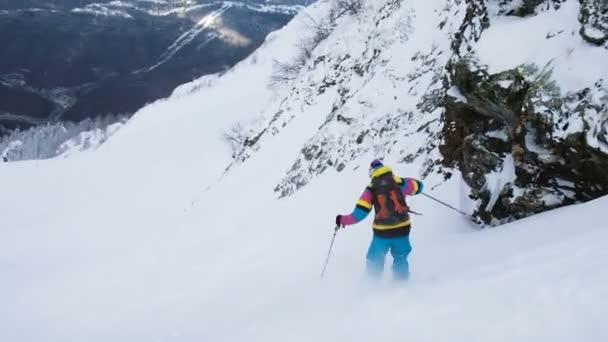 Lyžař v světlé barvě jde dolů z příkré hory, freeride v horách, pomalý pohyb.