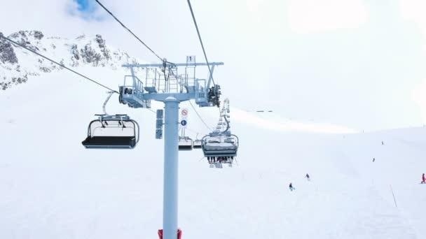 Blick vom offenen Lift in Bewegung nach oben, Vierer-Lifte funktionieren im Skigebiet, Abfahrts- und Snowboard-Touristen, Zeitlupe.
