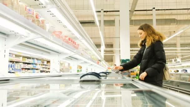 Giovane donna che sceglie un prodotto dal frigorifero in store