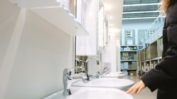 Žena si vybírá zrcadlové skříňky pro koupelny v úložišti stavební