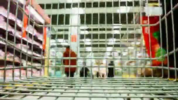 Time-lapse shot from the grocery cart in the supermarket, an empty cart skates in the store - the concept of economy