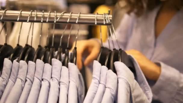 Žena v obchodě s oblečením si vybere košili
