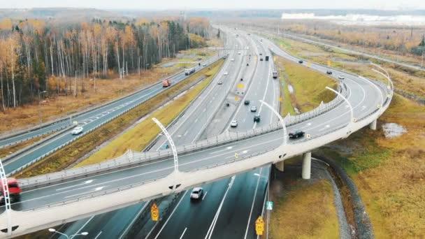 automobily jet rychle na široké dálnici a nadjezd silnici na podzim