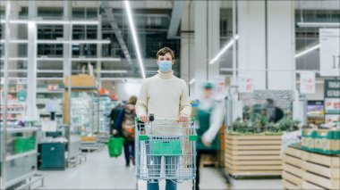A man in a medical mask stands in a supermarket with a food cart