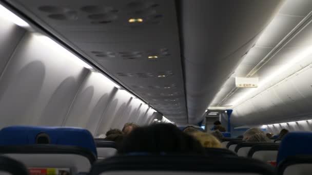 lidé sedí v několika řadách v pohodlném letadle