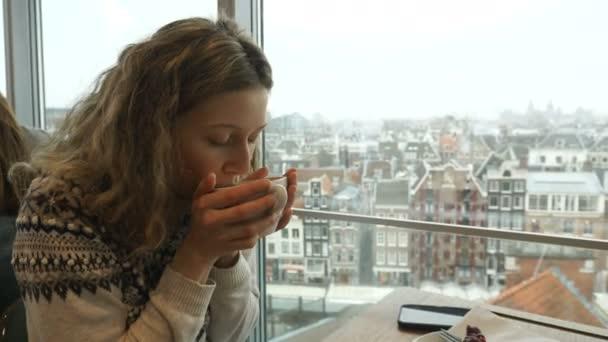 mladá žena popíjí kávu a dívá se na panorama Amsterdamu