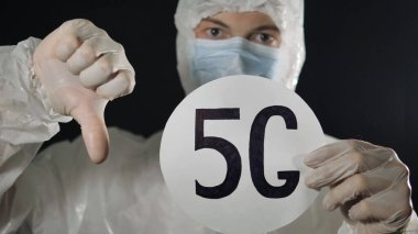 Man in a medical mask, rubber gloves and a protective suit raises the 5 g sign and shows his thumb down. 5 g networks spread the coronavirus. Coronavirus pandemic. stock vector