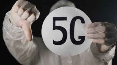 A man in a protective suit and medical mask raises the 5 g network sign and shows a thumb down on a dark background close-up. The spread of kronavirus. Conspiracy theory. stock vector