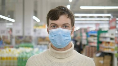 A young man puts on a medical mask to protect himself from the epidemic