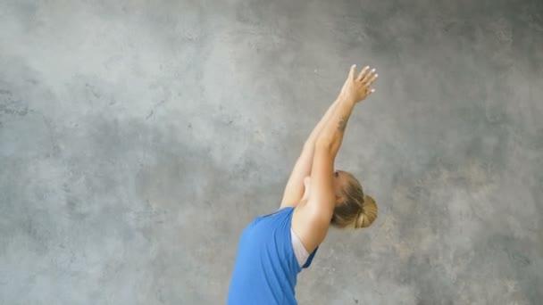 dívka dělá jógu Surya Namaskar v lehkém studiu