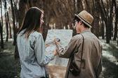 mladý pár turisty s mapou v lese