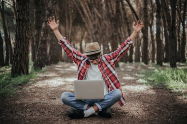 young man using laptop in forest