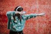 Žena, která dělá dab na ulici, poslouchat hudbu, na její sluchátka a s chytrým telefonem
