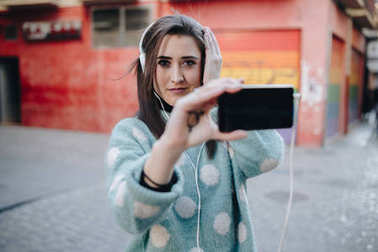 Beautiful woman listening to music with headphones and taking a selfie in the street