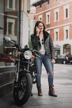Biker woman talking and using mobile phone