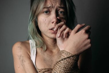 Scared woman with bound hands