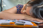 Exhausted office lady falling asleep on paperworks at workplace
