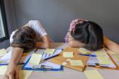 Tired women sleeping on desk full sticky notes